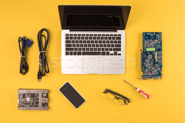 top view of laptop, smartphone, eyeglasses and wires on yellow Stock photo © LightFieldStudios