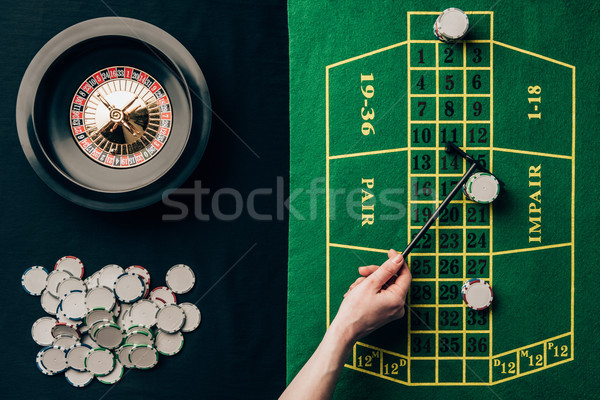 Woman moving chips on casino table with roulette Stock photo © LightFieldStudios