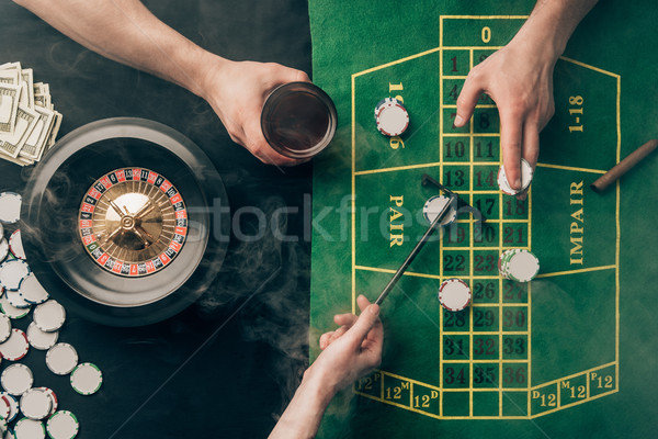 Smoke over people placing bets while playing roulette on casino table Stock photo © LightFieldStudios