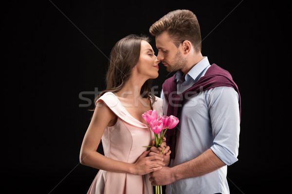 portrait of bonding couple in love with tulips bouquet in hands on black, international womens day c Stock photo © LightFieldStudios