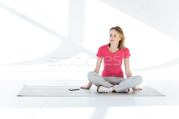 Young pensive woman sitting on yoga mat with smartphone and looking away Stock photo © LightFieldStudios
