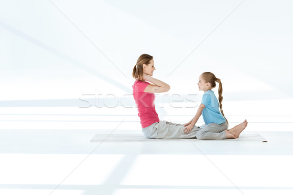 Stock photo: Side view of smiling daughter training happy mother on yoga mat