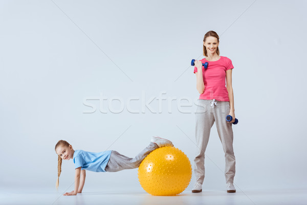sporty mother with dumbbells and daughter with fitness ball excising together  Stock photo © LightFieldStudios