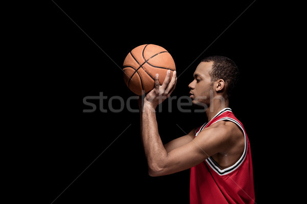Side view of young man basketball player with ball on black Stock photo © LightFieldStudios