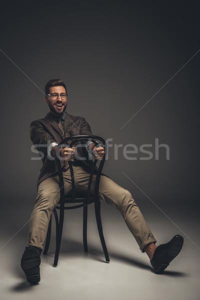 Férfi öltöny ül szék visszafelé nevet Stock fotó © LightFieldStudios