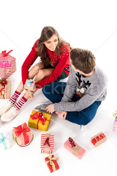 couple sitting among christmas gifts Stock photo © LightFieldStudios