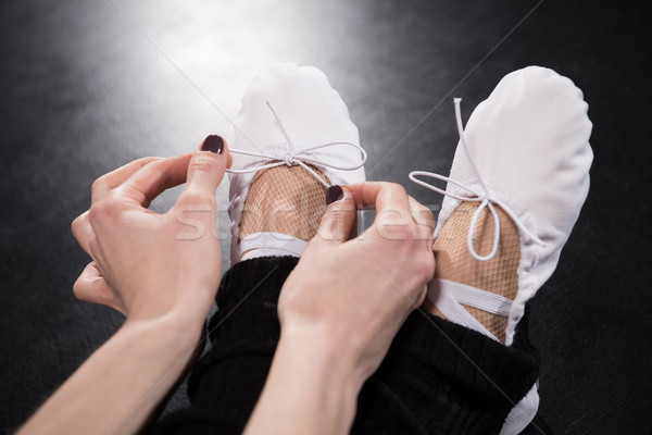 Close-up partial view of woman dancer tying ballet shoes on black Stock photo © LightFieldStudios