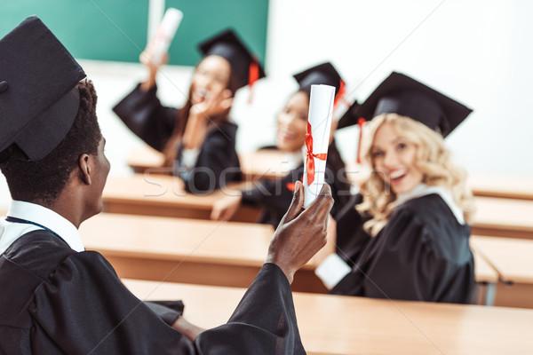 Több nemzetiségű diákok mutat boldog érettségi jelmezek Stock fotó © LightFieldStudios