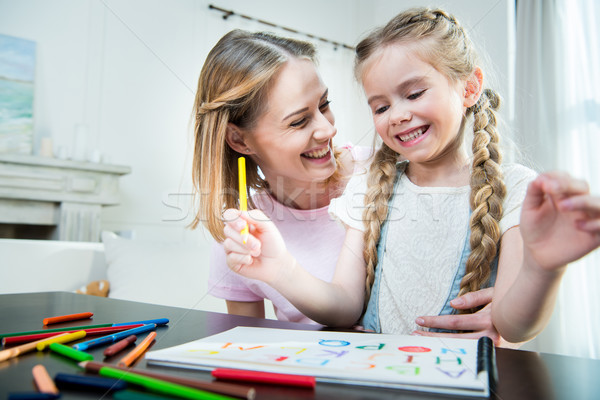 Happy mother and daughter hugging while drawing together at home Stock photo © LightFieldStudios