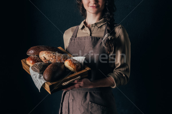 Stock photo: cropped shot of woman holding wooden box with loafs of bread isolated on black
