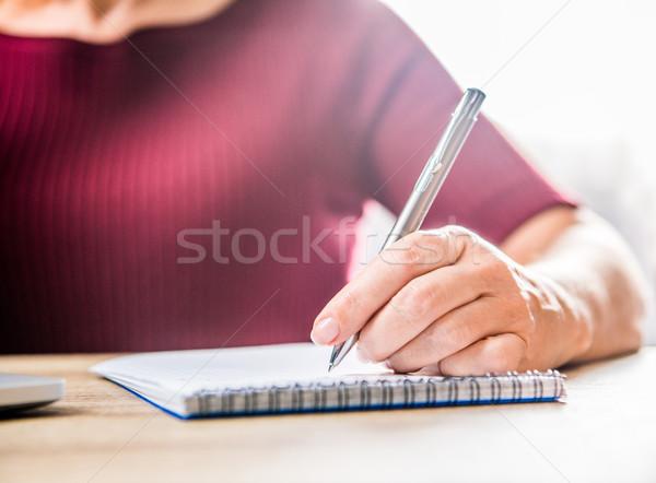 Woman writing in notebook Stock photo © LightFieldStudios