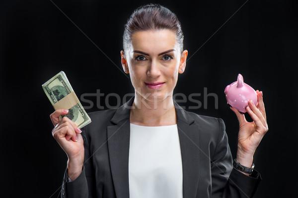 Businesswoman holding piggybank Stock photo © LightFieldStudios