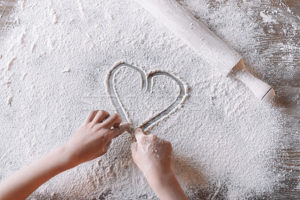 'Partial top view of child drawing heart symbol in flour on table, Mothers day concept Stock photo © LightFieldStudios