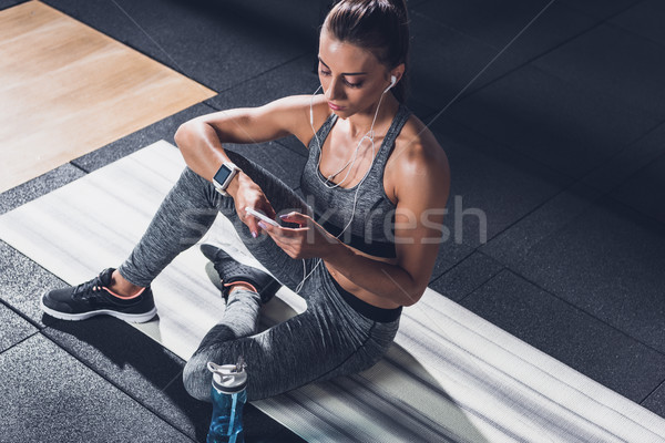 sportive woman using smartphone Stock photo © LightFieldStudios