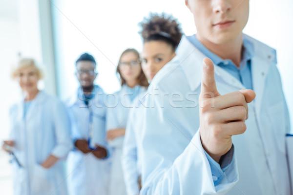 Médico indicação dedo jovem jaleco grupo Foto stock © LightFieldStudios