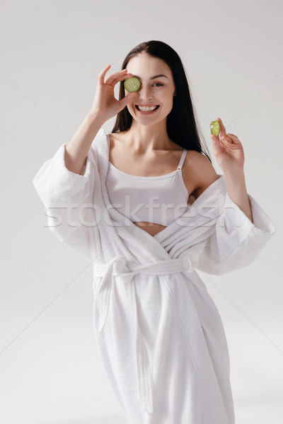 Smiling woman holding slices of cucumber Stock photo © LightFieldStudios