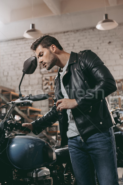biker in leather jacket with motorcycle Stock photo © LightFieldStudios
