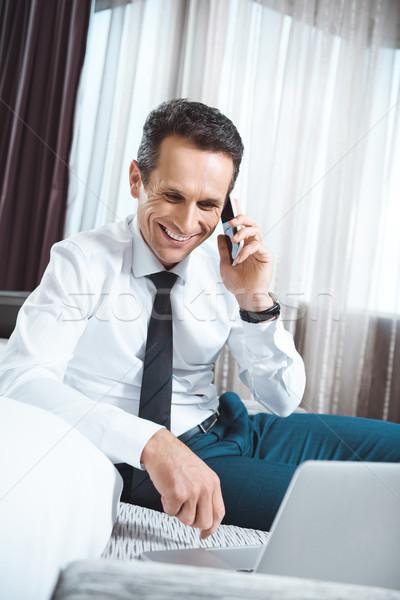 Işadamı konuşma telefon gülen dizüstü bilgisayar kullanıyorsanız oturma Stok fotoğraf © LightFieldStudios