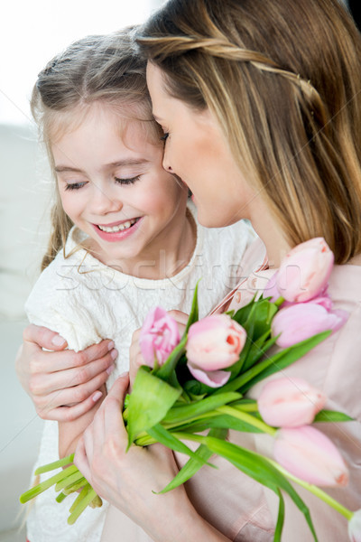 side view of happy mother with tulips hugging smiling daughter, mother's day concept Stock photo © LightFieldStudios