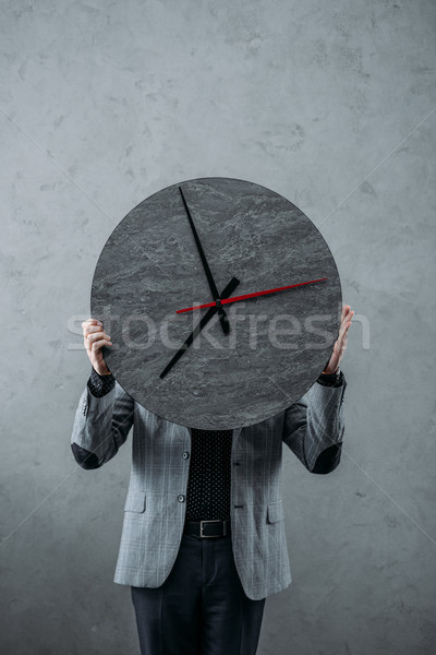 businessman holding clock Stock photo © LightFieldStudios