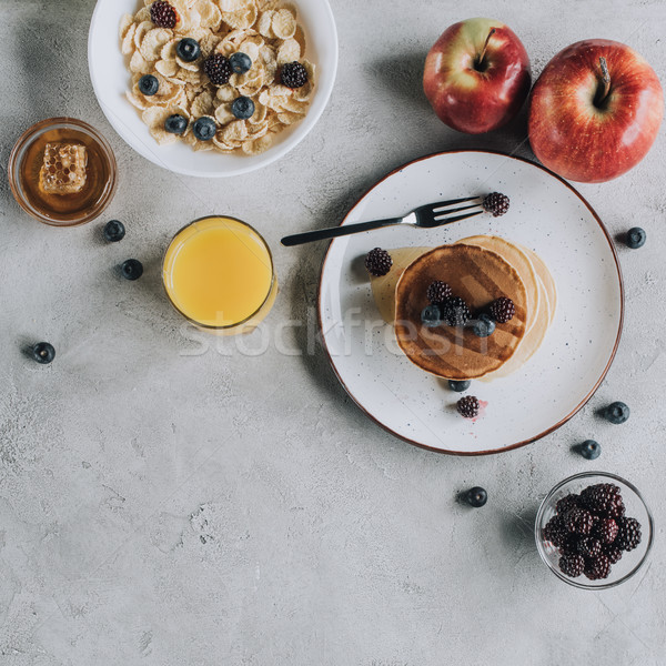 top view of sweet gourmet breakfast with pancakes, fruits, honey and muesli on grey    Stock photo © LightFieldStudios
