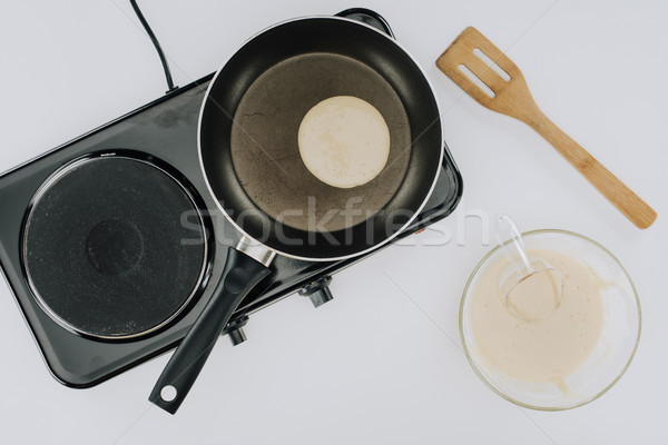 cropped shot of pancake cooking on frying pan and dough in bowl on grey Stock photo © LightFieldStudios