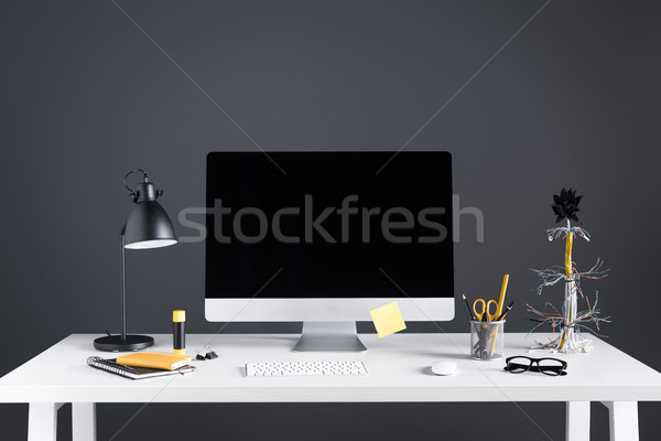 desktop computer with blank screen, lamp and office supplies on table on grey Stock photo © LightFieldStudios