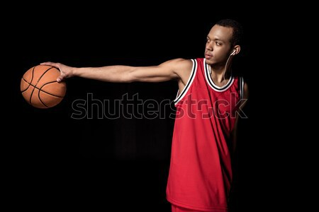 Young athletic basketball player in uniform holding ball on black Stock photo © LightFieldStudios