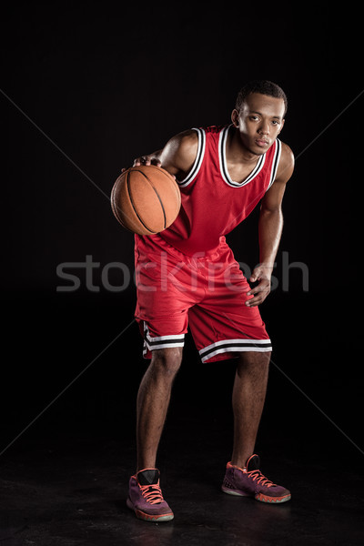 african sporty man in sports uniform playing basketball on black Stock photo © LightFieldStudios