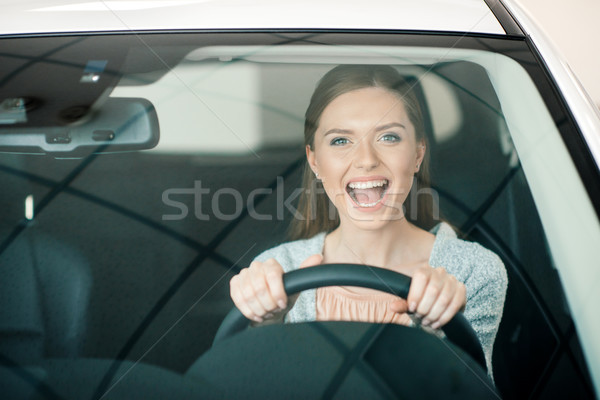 excited young woman sitting in new car and looking at camera Stock photo © LightFieldStudios