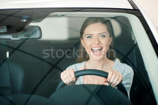 Izgatott fiatal nő ül új autó néz kamera Stock fotó © LightFieldStudios