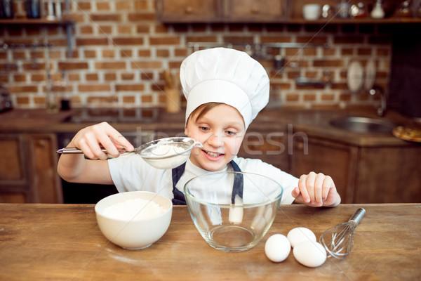 smiling little boy pouring flour in bowl Stock photo © LightFieldStudios