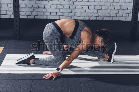 woman stretching leg on yoga mat Stock photo © LightFieldStudios