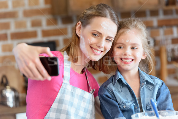 portrait of smiling mother and daughter making selfie while cooking at home Stock photo © LightFieldStudios