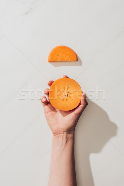 cropped image of woman holding persimmon piece on white Stock photo © LightFieldStudios