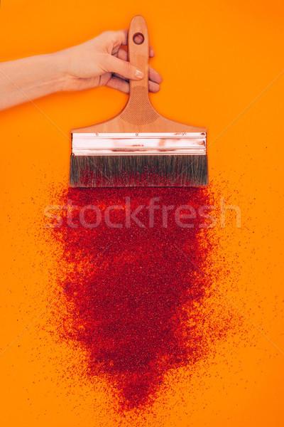 cropped image of woman holding brush above red sand isolated on orange Stock photo © LightFieldStudios