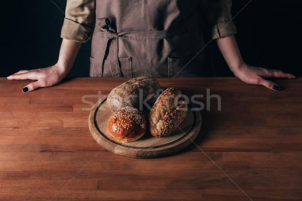 partial view of woman standing at table with loafs of bread on wooden cutting board Stock photo © LightFieldStudios