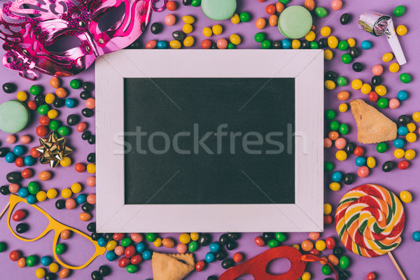 top view of arranged masquerade masks, candies, cookies and empty blackboard isolated on purple Stock photo © LightFieldStudios