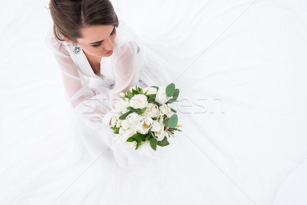 overhead view of young bride in dress holding wedding bouquet, isolated on white Stock photo © LightFieldStudios