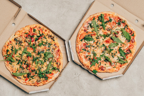 Hot Italian pizzas with arugula in cardboard boxes on light background Stock photo © LightFieldStudios