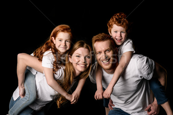 Happy redhead family in white t-shirts smiling isolated on black Stock photo © LightFieldStudios