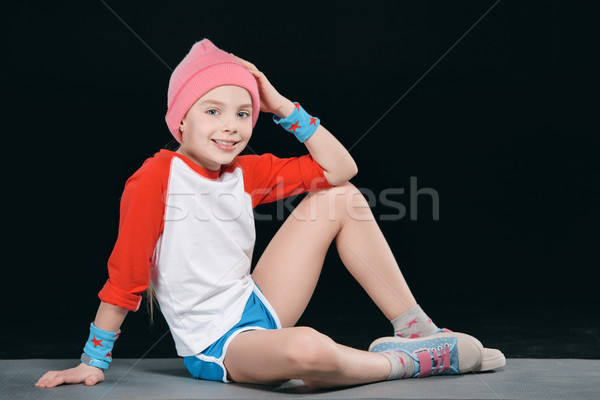 girl in sportswear sitting on mat isolated on black. 11 year old kids concept  Stock photo © LightFieldStudios