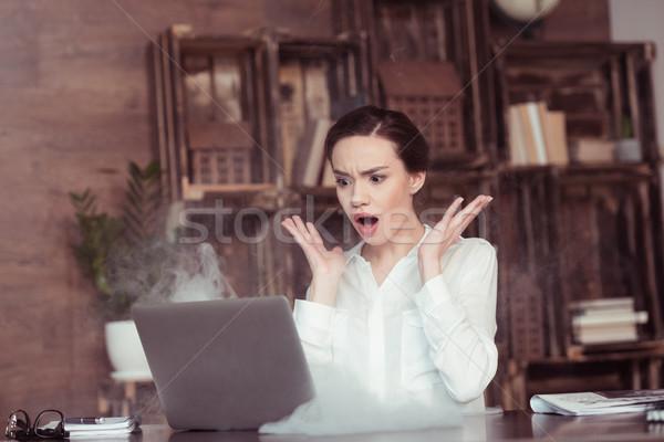 Megrémült fiatal üzletasszony néz laptop füst Stock fotó © LightFieldStudios