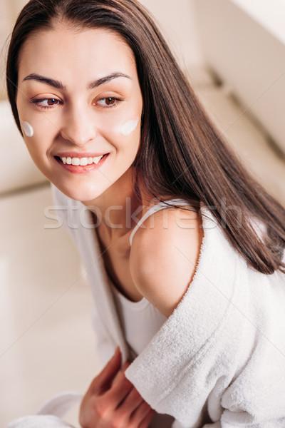 smiling woman with cream on face Stock photo © LightFieldStudios