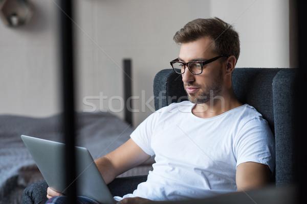 Homme fauteuil utilisant un ordinateur portable jeunes bel homme maison Photo stock © LightFieldStudios