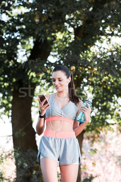 スポーツウーマン イヤホン スマートフォン 笑みを浮かべて アスレチック 若い女性 ストックフォト © LightFieldStudios