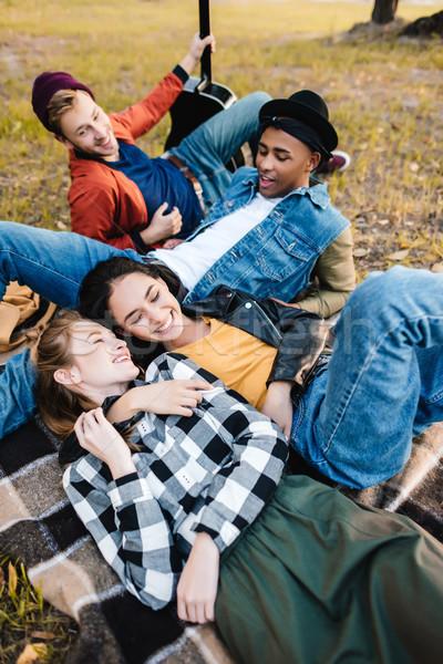 Multikulturális barátok pihen park csoport boldog Stock fotó © LightFieldStudios