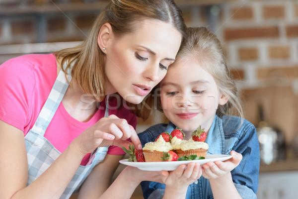 portrait of mother and daughter holding homemade cupcakes with strawberries Stock photo © LightFieldStudios