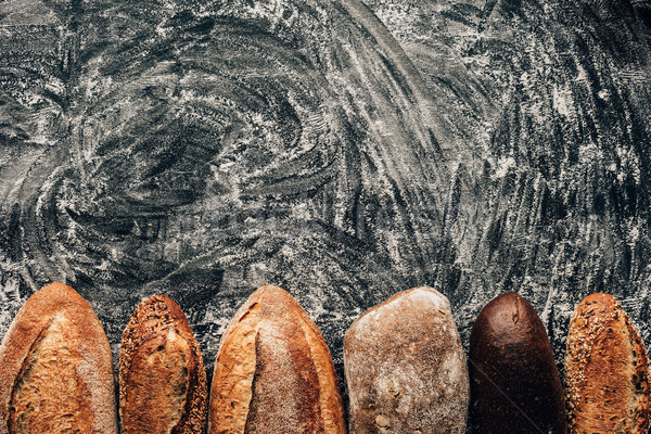 top view of arranged loafs of bread on dark tabletop with flour Stock photo © LightFieldStudios
