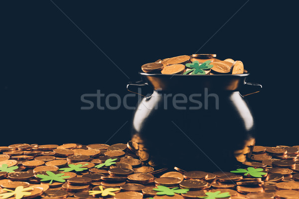 black pot with golden coins and shamrock isolated on black, st patricks day concept Stock photo © LightFieldStudios